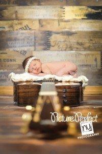 newborn baby posed on guitar