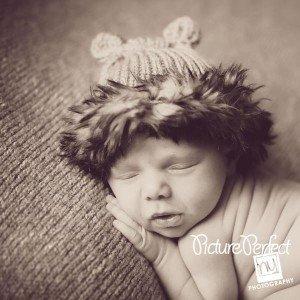 newborn baby wearring furry hat