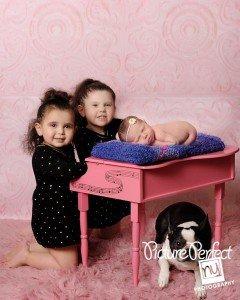 newborn baby posed on piano