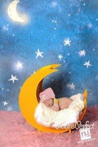 newborn baby posed on moon