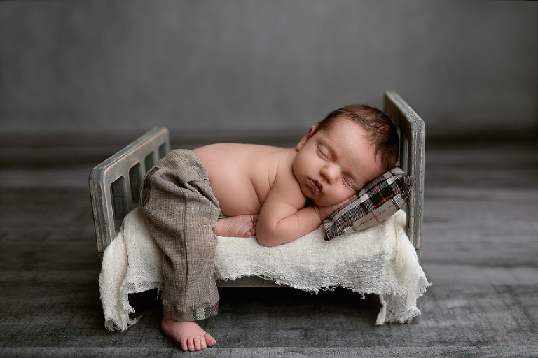 nyc newborn photographer baby in the bed