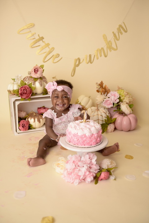 girl eating cake smash at little pumpkin first birthday photo portrait session