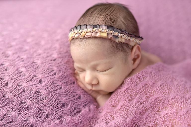 newborn baby girl underthe covers sleeping