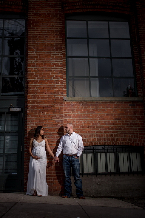 The gorgeous couple poses in front of a historic brick wall.