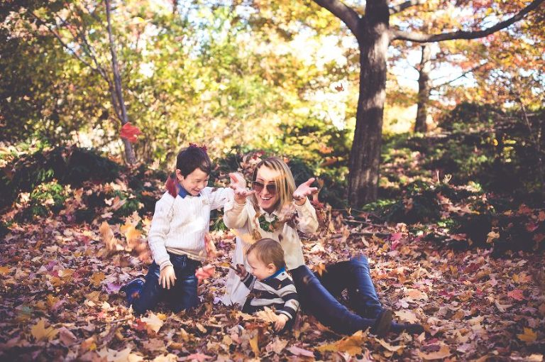This gorgeous family plays in the fall leaves, creating a beautiful and bonding family picture.
