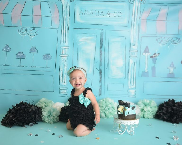 Amalia poses by her custom cake.
