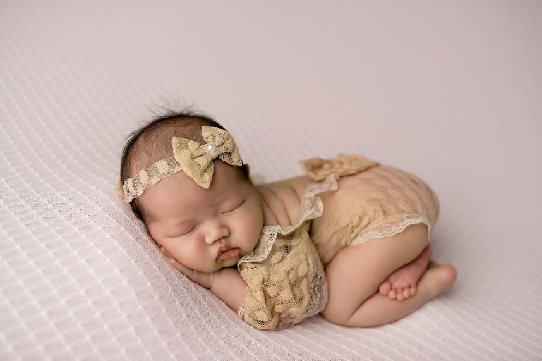 This cute babe lies bum up, comfy on a pale pink linen.