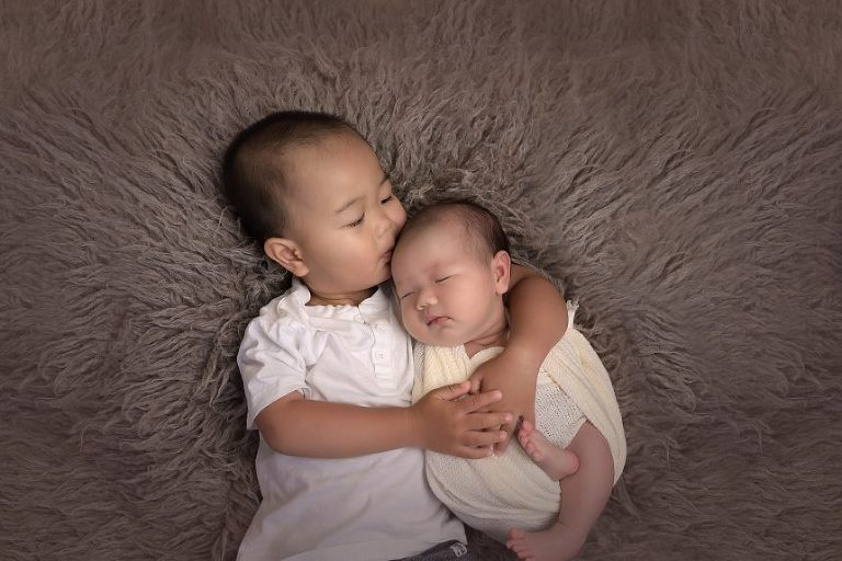 Big brother hugs his new baby brother. Sibling love is the sweetest love.