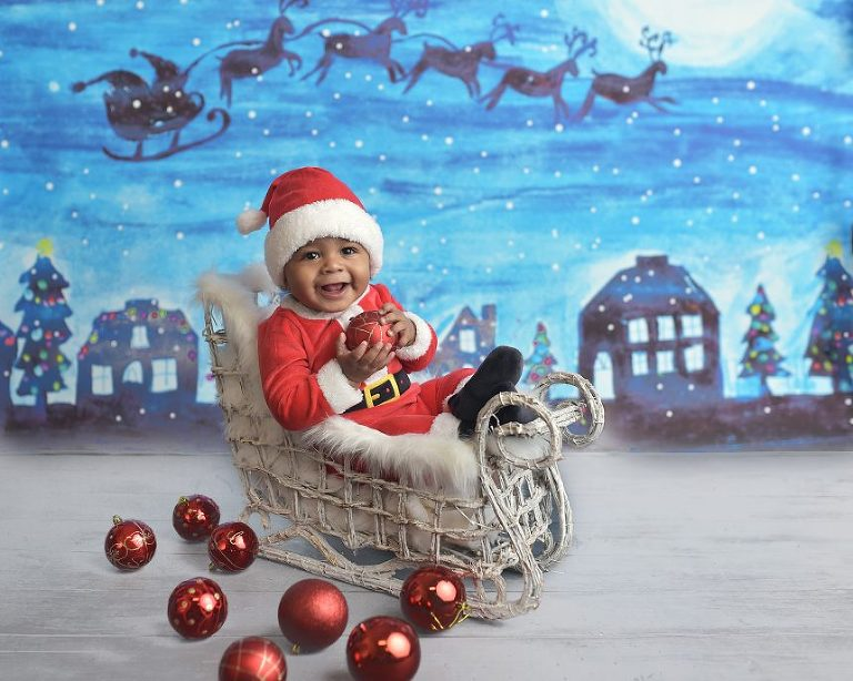 This precious baby boy shows his Christmas spirit riding in a sleigh with Santa's reindeer!