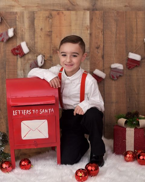 This little boy patiently awaits Santa's reply!