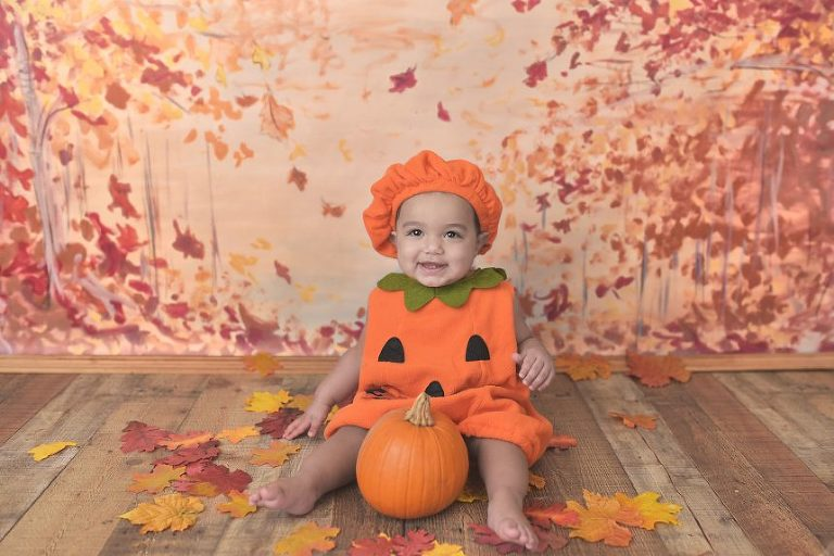 This cutie poses with a pumpkin outfit and a pumpkin!