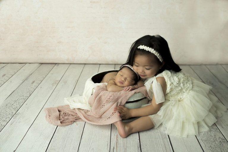 Big Sis, Harper, holds her little sister.