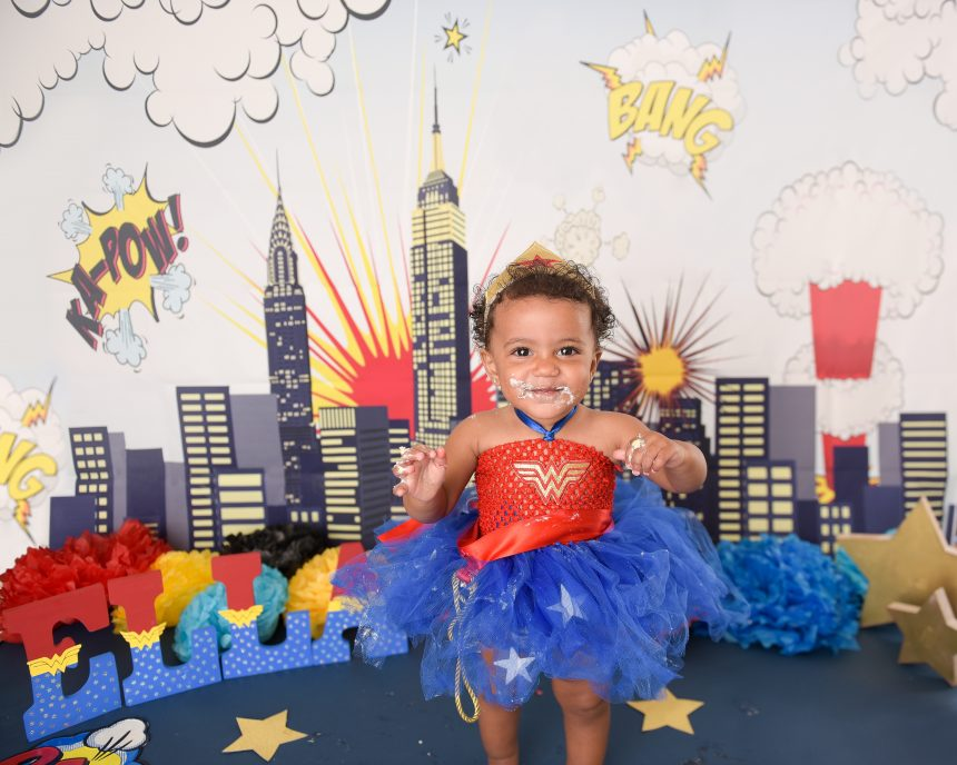 Ella poses in front of her Wonder Woman cake smash session!