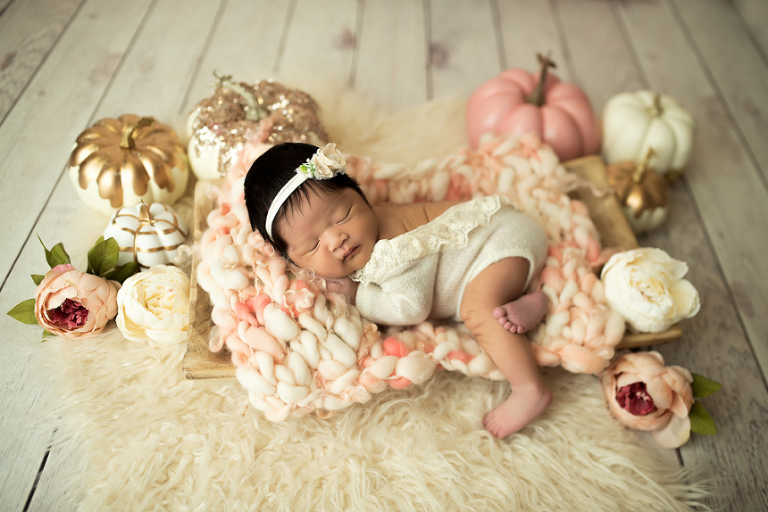 A newborn lays among pumpkins.