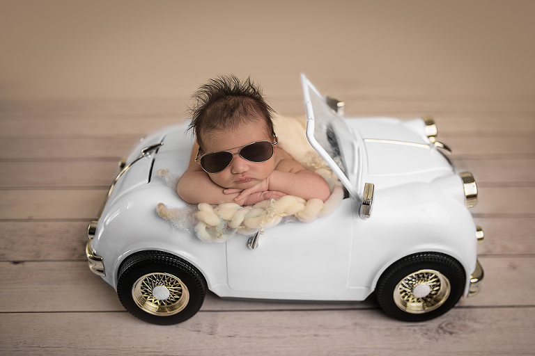 picture perfect ny nyc newborn photographer captures newborn baby crusing in convertable duing a newborn session