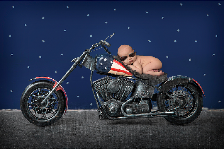 Newborn baby boy on the motorcycle chopper with American Flag